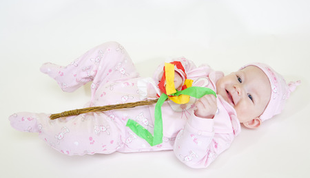 6 12 months: lying down baby girl holding a willow stick (Czech Easter) Stock Photo