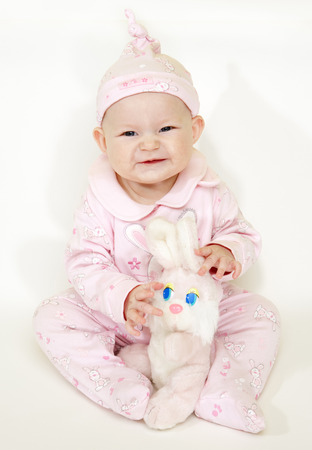 6 12 months: sitting baby girl with a rabbit toy