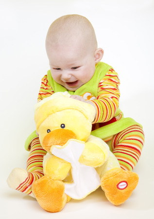 6 12 months: sitting baby girl with a duck toy