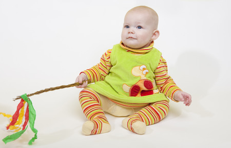 6 12 months: sitting baby girl holding a willow stick (Czech Easter) Stock Photo