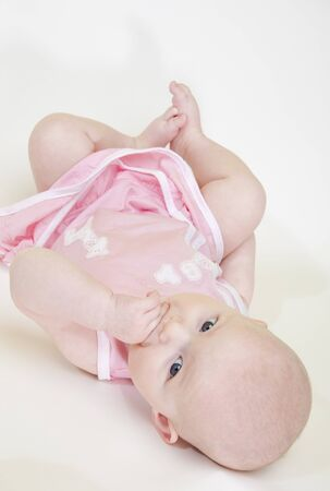 defenceless: lying down baby girl Stock Photo