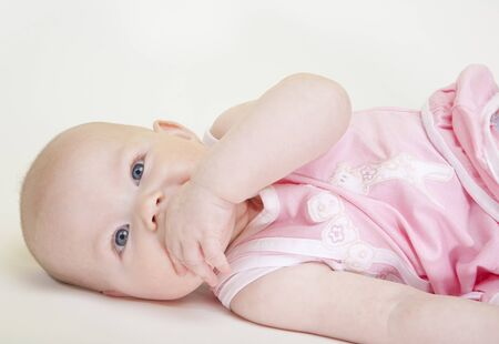 6 12 months: portrait of lying down baby girl