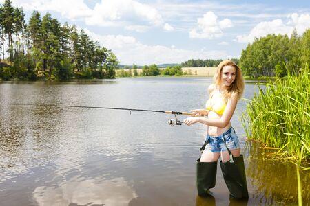 jeune femme dans un étang de pêche pendant l'été