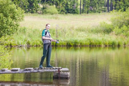 jeune femme la pêche sur la jetée à l'étang