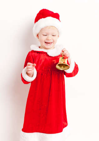 christmas motive: little girl as Santa Claus with a bell Stock Photo