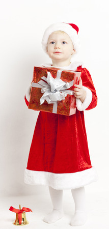 little bell: little girl as Santa Claus with a bell and Christmas present