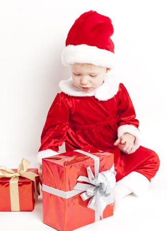 christmas motive: little girl as Santa Claus with Christmas presents Stock Photo