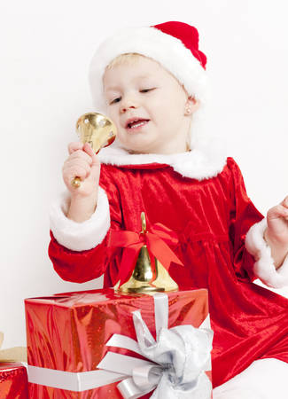 christmas motive: little girl as Santa Claus with bells and Christmas present Stock Photo