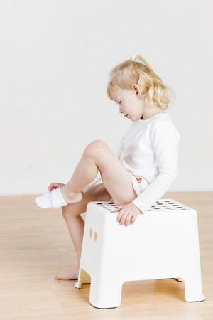 niños vistiendose: Niña que se sienta el cambio de la ropa