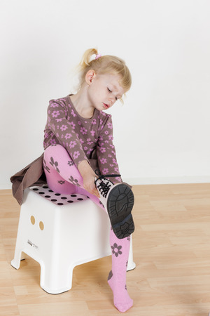 stool: little girl putting on boots