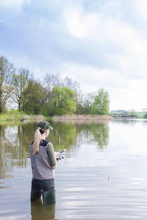fisherwoman: woman fishing in pond in spring