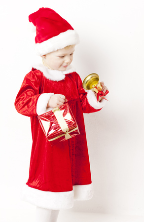 christmas motive: little girl as Santa Claus with a bell and Christmas present