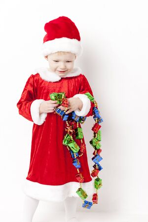 christmas motive: little girl as Santa Claus with Christmas chain Stock Photo