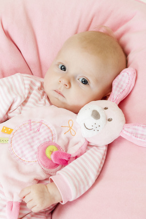 three months old: portrait of three months old baby girl holding a toy
