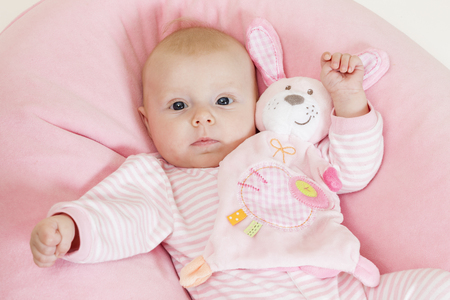 carelessness: portrait of three months old baby girl with a toy