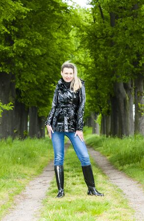 woman wearing rubber boots in spring alley Stock Photo