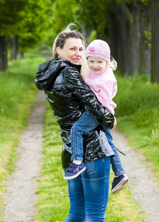 niñas sonriendo: portrait of mother with her little daughter in spring alley Foto de archivo