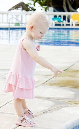 baby facial expressions: little girl at swimming pool, Tobago Stock Photo