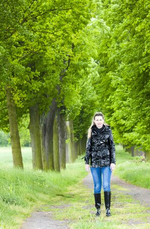rubber boots: woman wearing rubber boots walking in spring alley