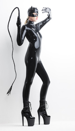 domina: standing woman wearing latex clothes with a whip