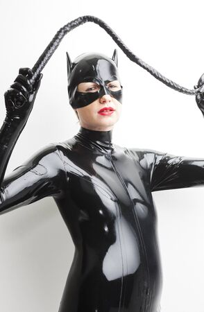dominant woman: portrait of standing woman wearing latex clothes with a whip