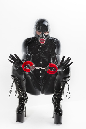 fetishism: sitting woman wearing latex clothes with handcuffs