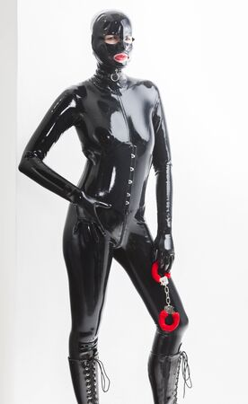 fetishistic: standing woman wearing latex clothes with handcuffs