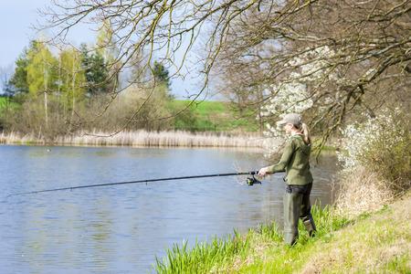 fisherwoman: woman fishing at pond in spring