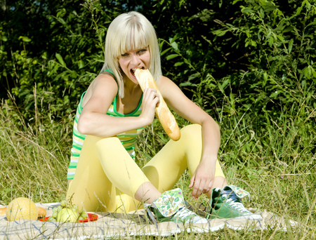 blond haired: woman with a baguette at a picnic