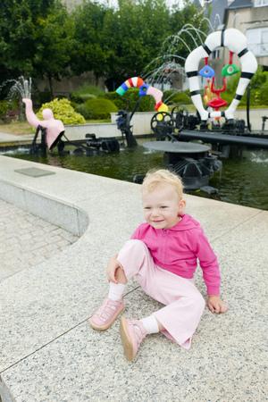 chinon: littlle girl sitting by modern fountain by Niki de Saint Phalle, Chateau-Chinon, Burgundy, France Stock Photo