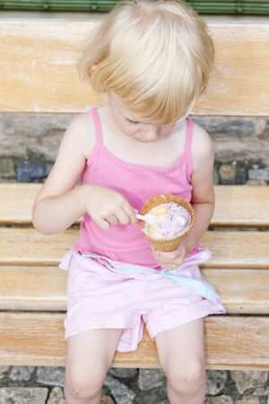 tempt: little girl with ice cream sitting on bench