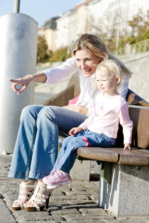 mother on bench: mother with her little daughter sitting on bench