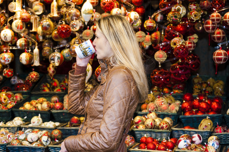 christkindlmarkt: woman drinking hot wine at Christmas market, Vienna, Austria Stock Photo