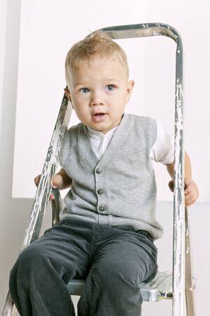 retrato de un niño pequeño que se sienta en la escalera