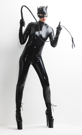 fetishistic: standing woman wearing latex clothes with a whip