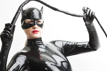 extravagance: portrait of standing woman wearing latex clothes with a whip