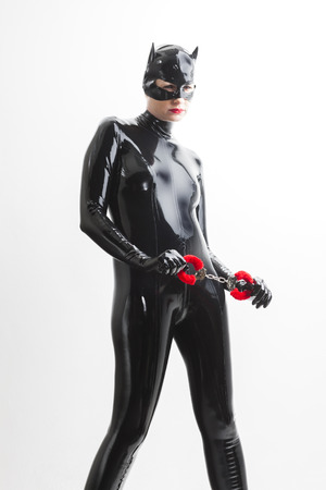 fetishism: standing woman wearing latex clothes with handcuffs