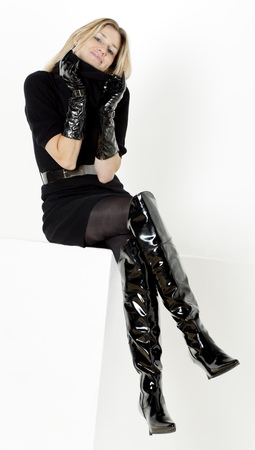 black boots: sitting woman wearing black dress and fashionable boots