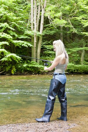 wellingtons: woman fishing at river Stock Photo