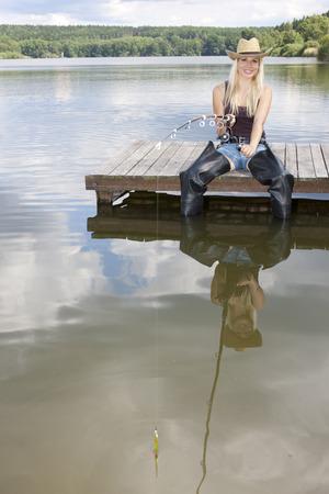 femme de pêche assis sur la jetée