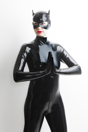 latex: portrait of standing woman wearing latex clothes