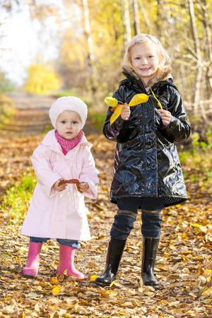 niñas sonriendo: niñas con botas de goma en la naturaleza otoñal