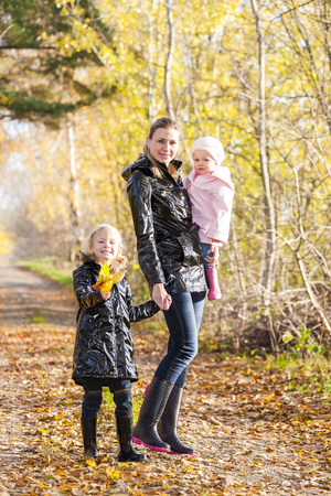 cradling: mother with her daughters in autumnal nature