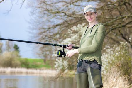 pêche à la femme à l'étang au printemps