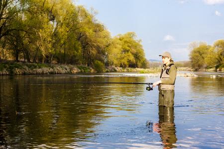 fisherwoman: woman fishing in the river in spring