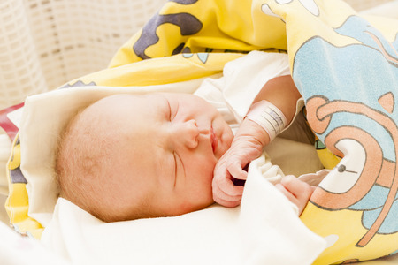 labelling: portrait of a newborn baby girl in maternal hospital Stock Photo