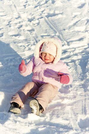 little girl sitting: little girl sitting on snow Stock Photo