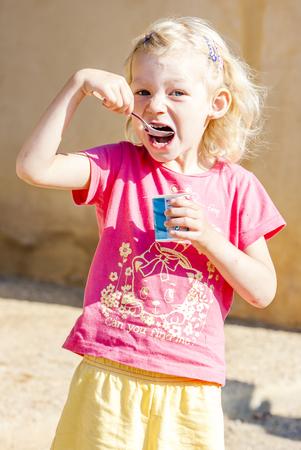 eating yogurt: little girl eating yogurt Stock Photo