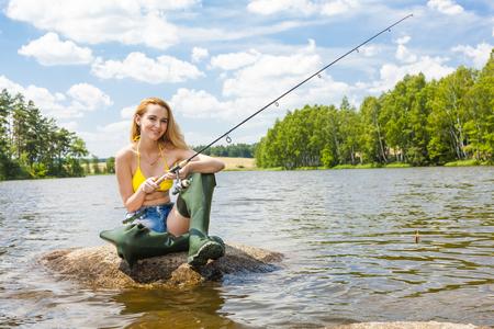 jeune femme dans un étang de pêche pendant l'été Banque d'images