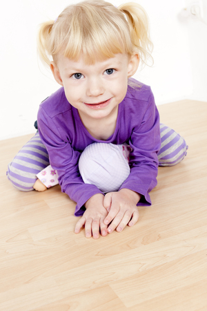 kneel down: portrait of little girl playing with a doll